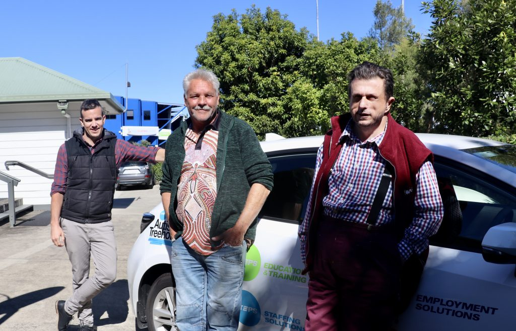 3 men from STEPS stand together outside leaning against car