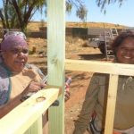 Two women smile while constructing a cubby house
